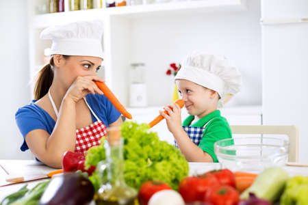 boy lady: Mother and son putting carrots on nose and playing together