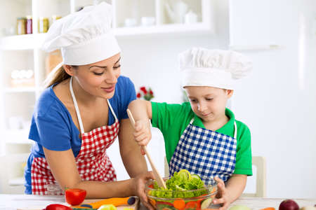 boy lady: Mother and son prepare lettuce together Stock Photo
