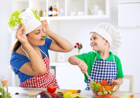 母と子を持つ野菜と一緒に遊んでのキッチンで楽しいし、台所で昼食の準備 写真素材