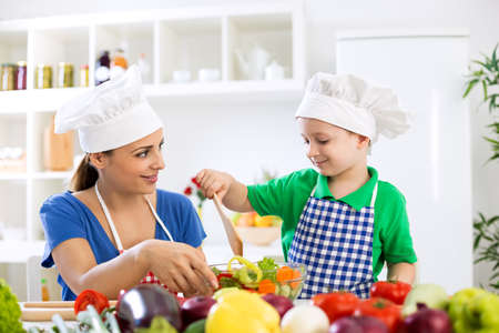 home cooking: Mom with kid making lettuce at kitchen