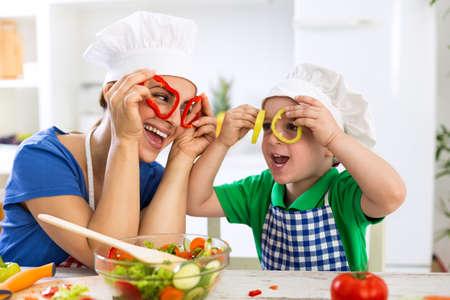 Gelukkige familie spelen met groenten in de keuken thuis Stockfoto