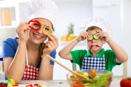 Family have fun in the kitchen with vegetables Imagens