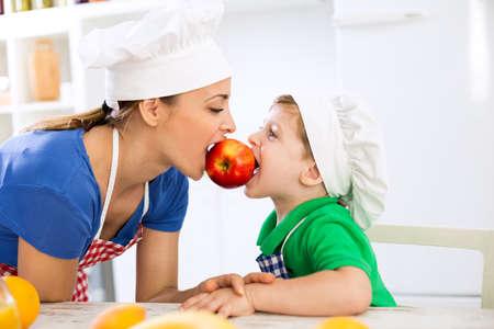 niños comiendo: Madre e hijo que comen la manzana juntos roja fresca en la cocina Foto de archivo
