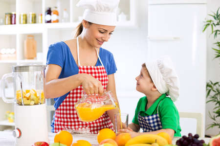 Beautiful happy mother pour orange juice to her child boy in kitchen Stockfoto