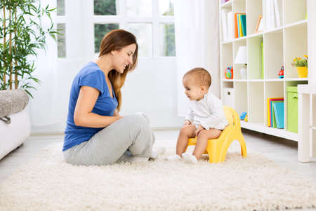 Beautiful mother learning little child how to sitting on potty at home