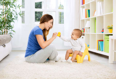 Baby sitting on potty and playing with smiling beautiful mother at home Standard-Bild