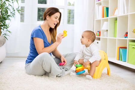 family indoors: Cute baby growing up and leaving diapers Stock Photo