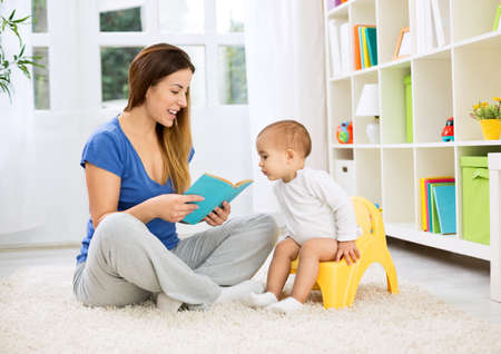 Cute baby sitting on bedpan and listening kid story with mom