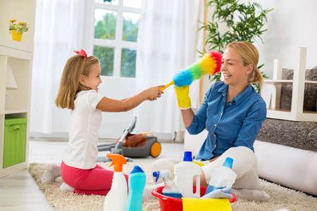 rubia: Sonriente mujer e hija hermosa disfrutan de limpieza de la casa