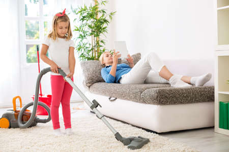exploitation: Lazy mother exploitation little child for cleaning home Stock Photo