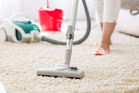 attractive female: Suction grey carpet cleaning with vacuum cleaner