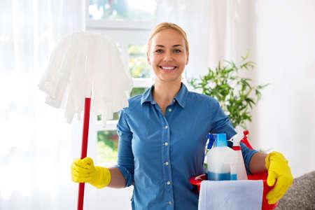 Glimlachende gelukkige huisvrouw klaar voor het schoonmaken thuis