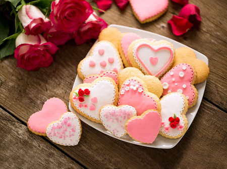 Beautiful tasty valentine day cookies and roses on vintage desk