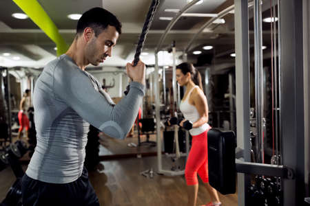 Strong muscular man and woman doing training with weight at gym Stock Photo