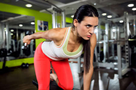man arm: Strong fitness angry girl doing training with weight at gym
