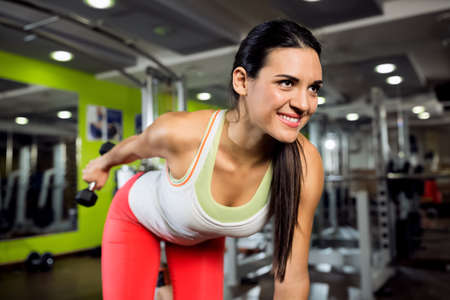 muscle girl: Smiling young girl workout at gym club with weight Stock Photo