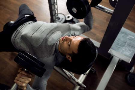 cuerpo hombre: Hombre durante el ejercicio de press de banca en el club de gimnasia Foto de archivo