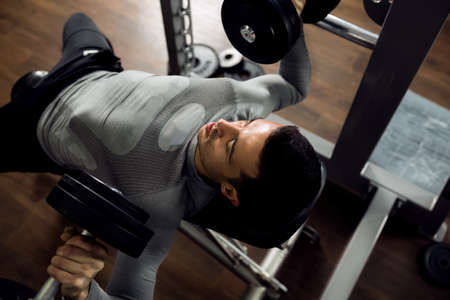body builder: Man during bench press exercise at gym club Stock Photo