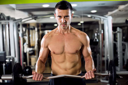 male body: Strong sexy man work out biceps at gym Stock Photo