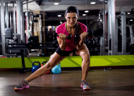 male body: Sexy attractive girl exercise with weight at gym Stock Photo