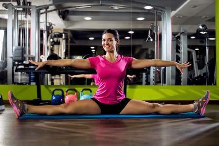 limber: Young smiling girl doing sword on mat at gym club Stock Photo