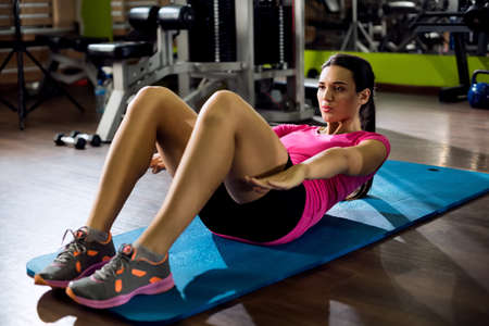 doing: Woman doing sit-ups at gym Stock Photo