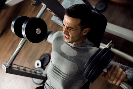 Strong man holding huge weight and working bench press at gym