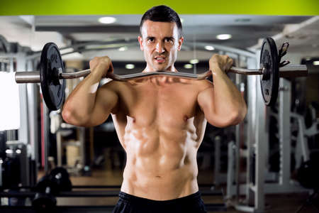 man gym: Fit male doing biceps exercise at gym