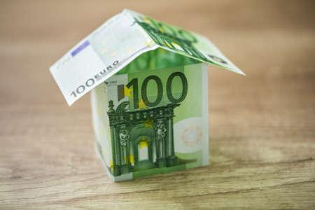 dinero euros: La casa, construida de billetes de 100 euros en el fondo de madera Foto de archivo