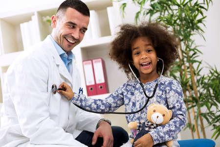 pediatrician: muchacha africana feliz jugando con el pediatra sonriendo