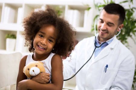 Beautiful smiling afro-american girl with her pediatrician at office