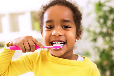 tooth cleaning: Little beautiful african girl brushing teeth, healthy concept