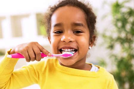 kinderen: Weinig mooi Afrikaans meisje tanden poetsen, gezonde concept