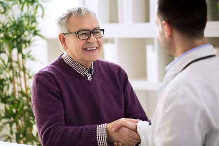幸せな健康的な古い男性揺れオフィスで医者と笑みを浮かべてください。