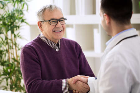 Smiling happy healthy old male shaking with doctor in office Standard-Bild