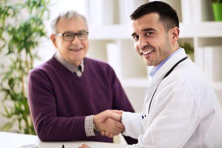 先輩患者と握手する医師 写真素材