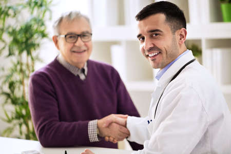 patient doctor: Doctor shakes hands with a senior patient