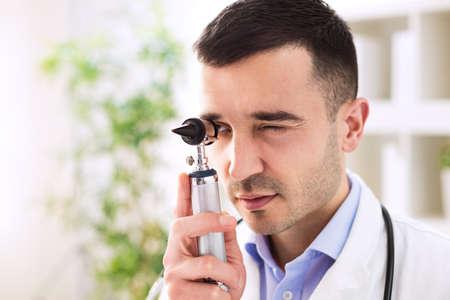 Young attractive doctor looking through otoscope