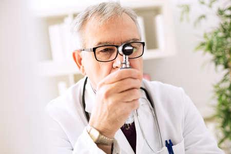 man doctor: Otolaryngologist specialist looking through otoscope Stock Photo