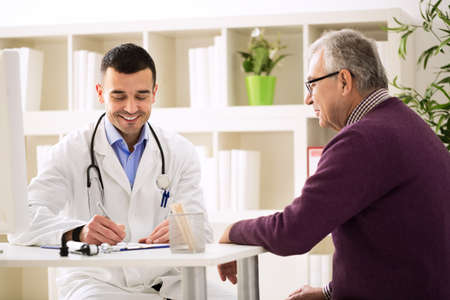 Specialist doctor and patient smiling and talking in office Banque d'images