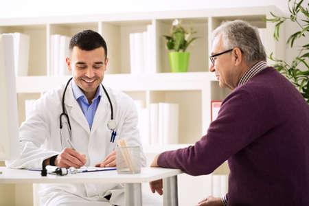 Specialist arts en patiënt glimlachend en praten in kantoor Stockfoto