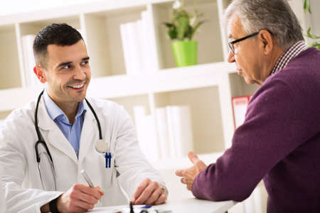 man doctor: Smiling success doctor listening carefully his senior patient in office