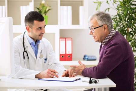Doctor listening to patient explaining his painful in his office Stockfoto