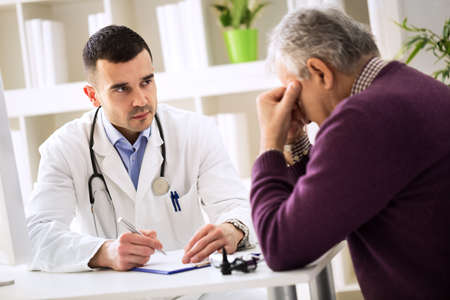 pains: Young doctor carefully listening senior patient about his pains