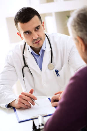Doctor listening to patient explaining about his painful Stockfoto