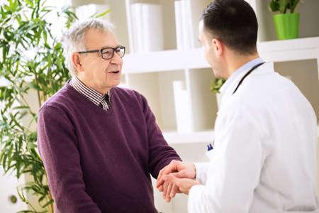 若い医者保持ハンドとリラックスした古い患者