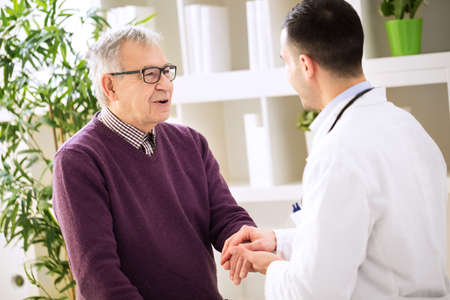 Young doctor holding hand and relaxing old patient
