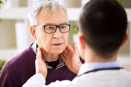 古い患者リンパ腺、のどの炎症を調べる医師