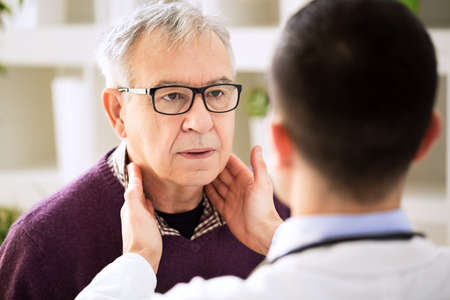 Doctor examining old patient lymph glands, throat inflammation Standard-Bild
