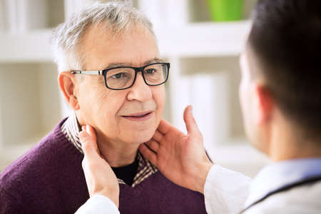 glands: Doctor examining old patient lymph glands, throat inflammation Stock Photo